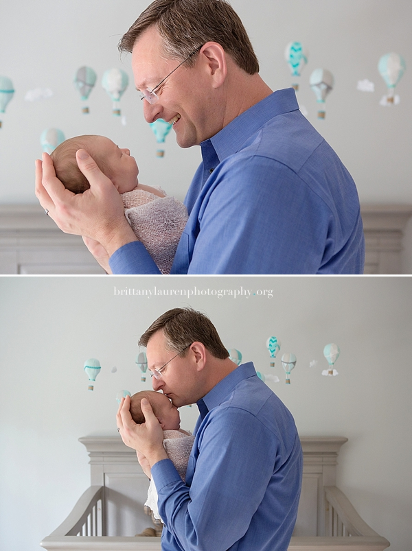 Newborn held by father